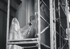 Beeldhouwwerk van John Paul II-paus achter beschermende folie in kerk stock foto