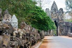 Beeldhouwwerken van de demonnen dichtbij door de ingang aan de tempel Bayon Stock Fotografie