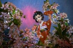 Beeldje dansende geisha in de tuin Sakura met decoratieve verlichting Stock Afbeeldingen