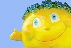 Beeldje gele zon met een glimlach op een blauwe achtergrond stock afbeeldingen