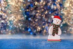 Beeldje van een sneeuwman op kleurrijke achtergrond bokeh Royalty-vrije Stock Fotografie