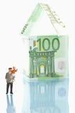 Beeldjes die zich voor huis van 100 euro nota's bevinden Stock Fotografie