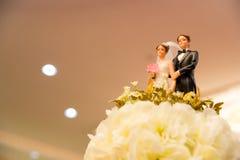 Beeldjes van de bruid en de bruidegom op een huwelijkscake Stock Foto's