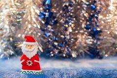 Beeldjestuk speelgoed Santa Claus op achtergrond van Kerstmis de kleurrijke bokeh Royalty-vrije Stock Fotografie