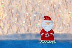 Beeldjestuk speelgoed Santa Claus op kleurrijke golvings bokeh achtergrond Stock Afbeelding