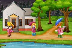 Beeldverhaal drie meisjes dragende paraplu onder de regen royalty-vrije illustratie