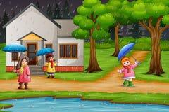 Beeldverhaal drie meisjes dragende paraplu onder de regen stock illustratie