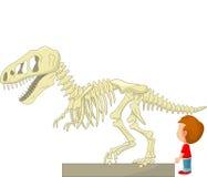 Beeldverhaaljongen met dinosaurusskelet bij het museum Stock Fotografie