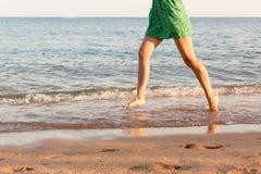 Been die van vrouw op strand met water het bespatten lopen De vakantie van de zomer benen van een meisje die in water op zonsonde stock afbeeldingen