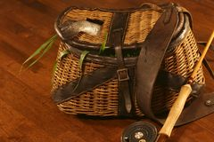 Been fishing, angling. Vintage creel with trout amidst grass, fly rod & reel Stock Photography