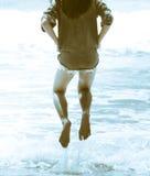 Been van meisjessprong boven de golf op het oceaanstrand Stock Afbeeldingen