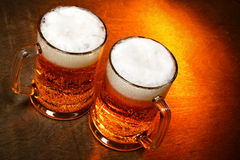 Beer. Two beer mugs close-up on wooden table Royalty Free Stock Images