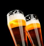 Beer. Two glasses of beer with froth over black background Stock Images