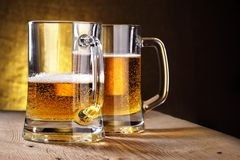 Beer. Two beer mugs close-up on wooden table Stock Images