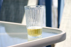 Beer. Glass of beer sitting on patio table Stock Image