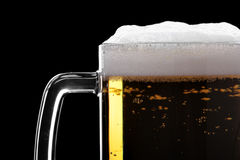 Beer. Mud with froth close-up isolated over the black background Royalty Free Stock Photo