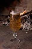 Beer. Pint of lager infront of a fireplace Royalty Free Stock Image