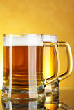 Beer. Mugs with froth over yellow background Stock Photos