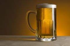 Beer. Glass of beer on orange background close up royalty free stock photos