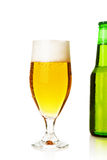 Beer. Glass of cold beer from a bottle in the background Stock Images