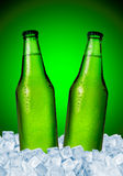 Beer. Bottles in ice over green background Royalty Free Stock Images