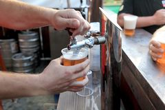 Beer. Pouring  beer to plastic glass from beer tap Stock Images