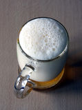 Beer. The full glass with foaming beer costs on a wooden table. The top point of shooting Stock Images