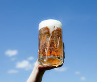 Beer. Mug of Beer with froth.Blue background Stock Photos