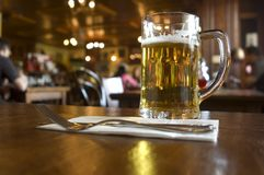 Beer. Glass of beer on the table in pub close up stock image