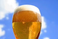 Beer. Overflowing from tall glass Stock Photo
