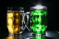 Beer. Two mugs of amber and green beer royalty free stock image