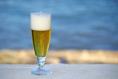 Beer. Glass of beer against blue sea Royalty Free Stock Photos