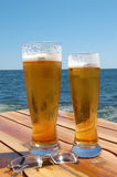 Beer. Two glasses of beer on sea background Royalty Free Stock Photography