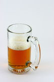 Half a mug of beer. Glass or mug half full of beer. White background stock photography