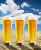 Beer. Three glasses with beer stand on a beach Stock Images