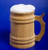 Beer. Wooden mug with beer on blue background royalty free stock image