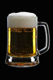 Beer. Mug of beer with froth over black background Royalty Free Stock Images