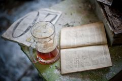 Beer in the abandoned place. Beer in the mug, placed on a table in the abandoned house. There are some old books in Russian language stock image