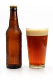 Beer aFoaming in glass and Bottle Royalty Free Stock Image