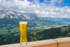 Beer in alps. Closeup of beer glass with tirol alps mountains in background royalty free stock images