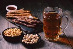 Beer and appetizers set. oktoberfest food, pub. Beer and appetizing snacks. table with two mugs of lager, wooden board with grilled sausages, garlic and sauce stock photo
