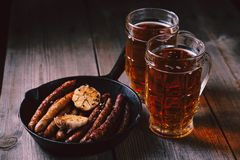 Beer and appetizing snacks.oktoberfest food, pub. Beer and appetizing snacks. table with two mugs of craft lager and frying pan with homemade grilled sausages stock photo