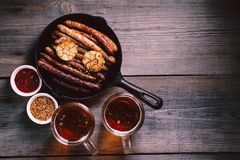 Beer and appetizing snacks.oktoberfest food, pub. Beer and appetizing snacks. table with two mugs of craft lager and frying pan with homemade grilled sausages royalty free stock photography