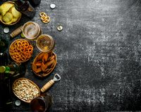 Beer and an assortment of different snacks with openers. On black rustic background royalty free stock photography