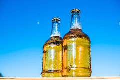 Beer on the background of the sky. Two bottles of beer standing on blue background Stock Photography