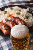 Beer on a background of snack sausages and sauerkraut. Vertical Stock Photo