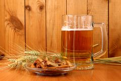 On the table is a beer froth in a mug and crunches on a plate stock image
