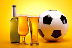 Beer and ball on yellow background Royalty Free Stock Photo