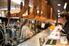 Beer bar pub tap, counter with blur pub background. Brussel Belgium.  Royalty Free Stock Photo