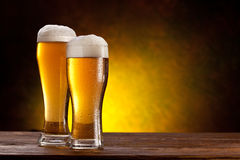 Beer barrel with beer glasses on a wooden table. Two glasses of beers on a wooden table. Dark yellow background royalty free stock photo